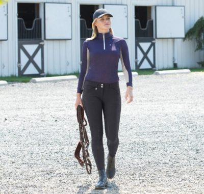 Chica con equipo de montar a caballo y cuadras al fondo